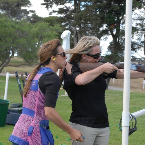 a woman shooting with the help of an instructor