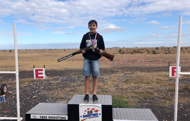 boy holding gun standing on podium