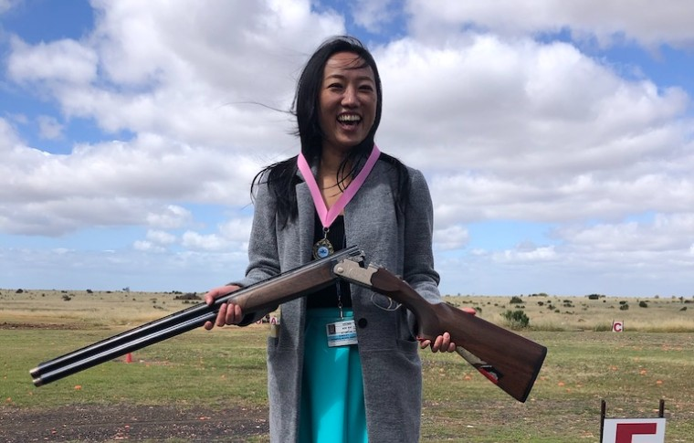 woman smiling while holding gun