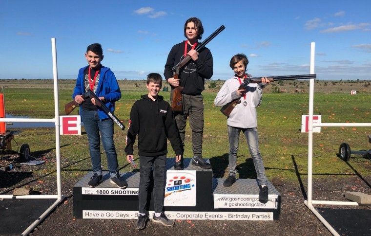 group of boys holding guns standing on podiums