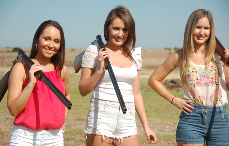 3 women smiling with guns over shoulders
