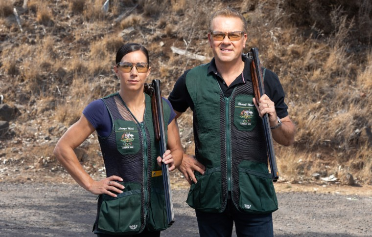 man and woman standing with guns over shoulders in professional shooting vests