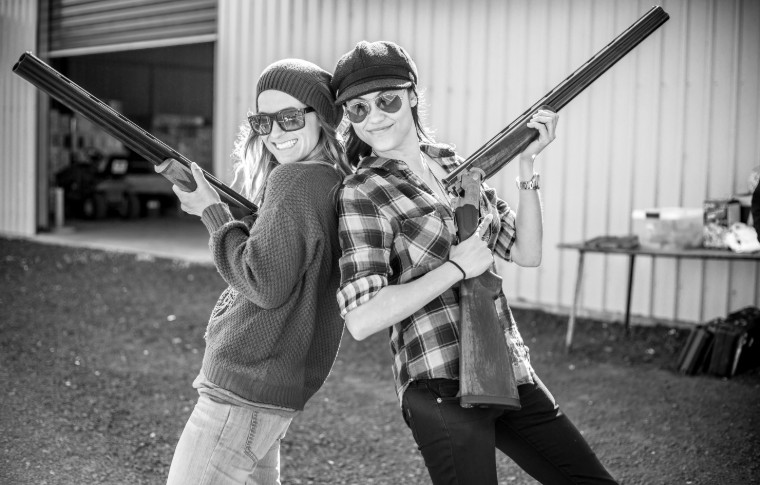 black and white photo of 2 girls holding guns and leaning on one another