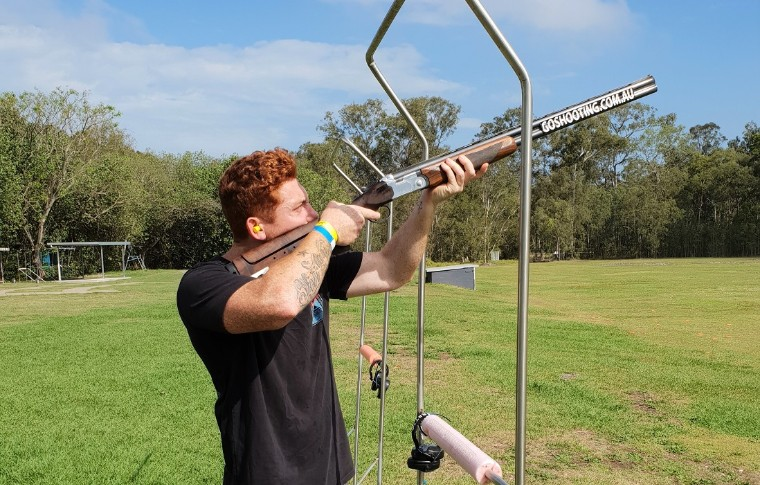 man with red hair shooting shotgun