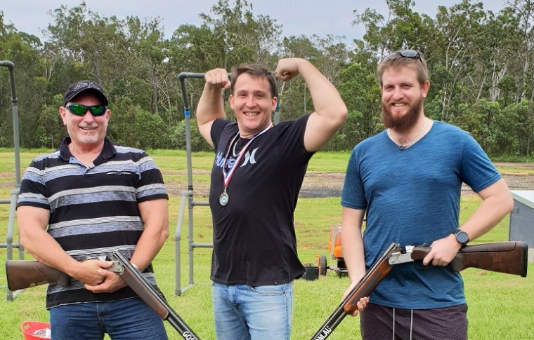 3 men smiling 2 holding guns and one flexing biceps