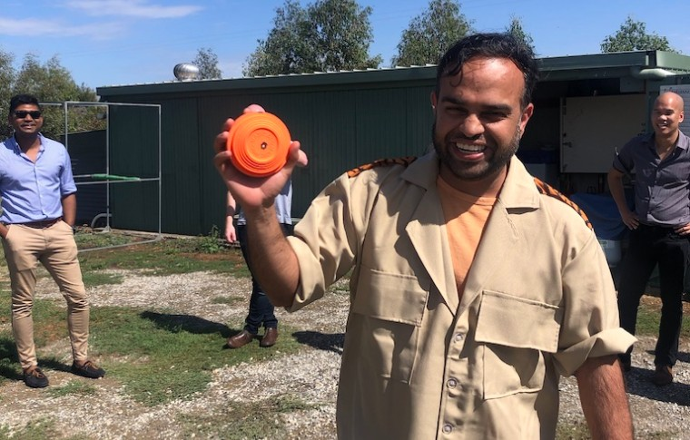 man smiling holding clay pigeon in hand